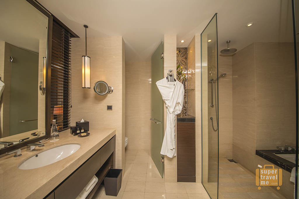 Bathroom with separate shower and bath in Room 1706 at Fairmont Jakarta