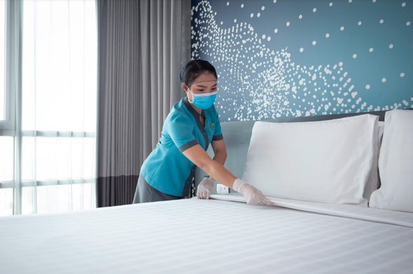 "As part of the ""ONYX Clean"" initiative, a room seal will be placed on every guest room door to indicate to arriving guests that their personal space has not been tampered with since being thoroughly cleaned and disinfected. Photo shows a housekeeping team member servicing a room at Shama Lakeview Asoke Bangkok."