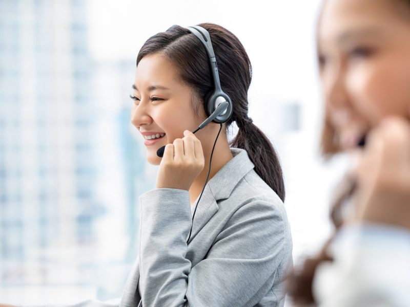 Istock/:Kritchanut Smiling beautiful Asian woman working in call center city office as a customer service operator with team